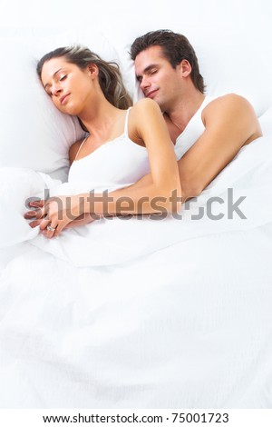 Young happy couple sleeping in bed. Love.