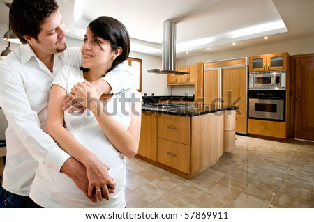 Young happy couple smiling at kitchen of new house