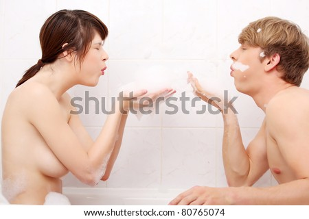 Young happy couple taking bath together.