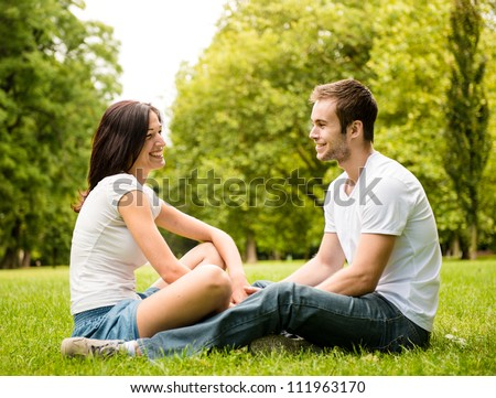 Young happy couple talking together outdoor - sitting on grass