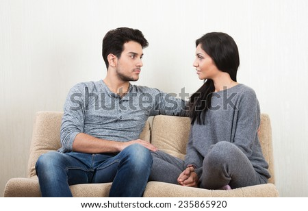Young happy couple talking together sitting on a sofa