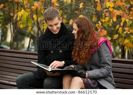 young happy couple with book on the bench. woman and man smiling.