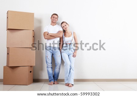 Young happy couple with boxes in apartment