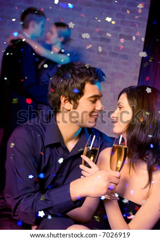 Young happy couple with champagne glasses at celebration