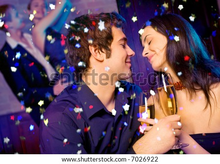 Young happy couple with champagne glasses at celebration - stock photo