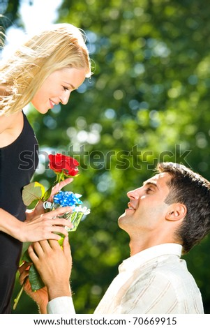 Young happy couple with rose and gift, outdoors