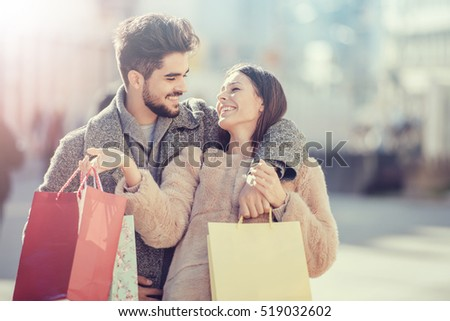 Shutterstock Young happy couple with shopping bags in the city.