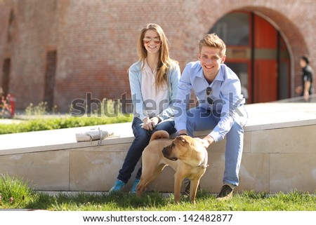 Young happy couple with their dog in the city
