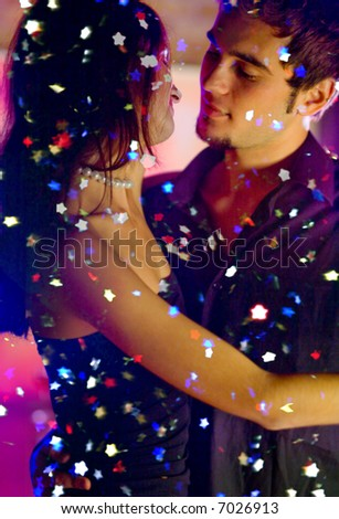 Young happy dancing amorous couple at celebration