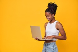 Young happy dark skinned teenager girl in white T-shirt isolated on a yellow background. African woman student, holds a laptop, writes a message to friends. Technology concept. Copy space.