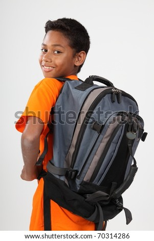 Young happy ethnic schoolboy wearing rucksack