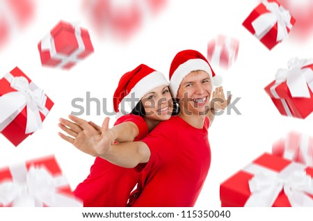 Young happy excited couple wear red Christmas hats and shirts, man and woman smiling with hands outstretched lifted upwards, gift box present fly around, isolated over white background
