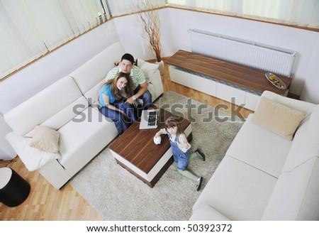 young happy family at bright and modern living room puting money in piggy bank and working on laptop computer on home finance