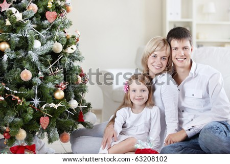 Young happy family at the Christmas tree at home