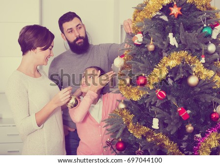 Young happy family decorating Christmas tree at home #697044100