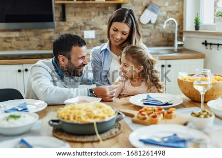 Young happy family having fun during lunch time at dining table.