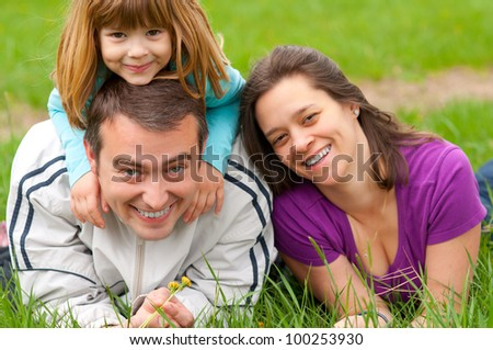 Young happy family having fun in the grass on beautiful spring day.