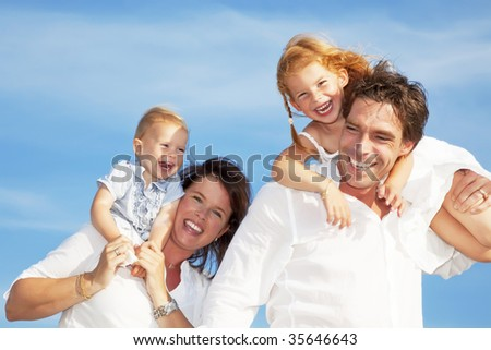 young happy family having fun outdoors, dressed in white and with blue sky in background