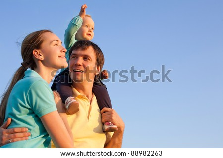 young happy family having fun outdoors with blue sky in background - stock photo