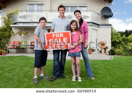 Young happy family holding sold sign outside their new house