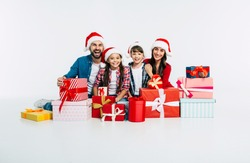 Young happy family in Santa hats with pile of christmas presents show it into the camera isolated on white background. New Year holidays