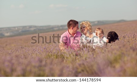young happy family of mother, father, daughter and dog sitting in the grass in a field of lavender. family portrait