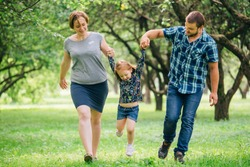Young happy family of three having fun in park. Cute little girl playing with mother and father outdoors. Happy parenting concept.
