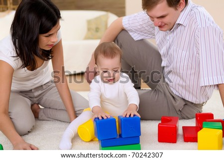 young happy family  playing with a baby in the living-room