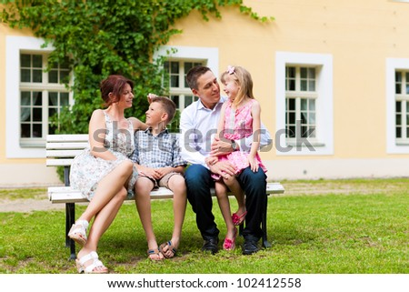 Young happy family sitting in the sun in front of their new home on a bench - it is a villa