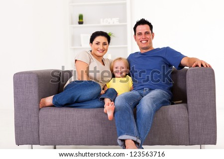 young happy family sitting on sofa at home