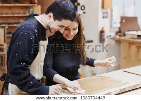 young happy family standing at a work bench in a carpentry workshop, process a tree a varnish. Family business. startup business. young specialist designer.