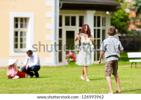 Young happy family - the children and the parents playing on the meadow