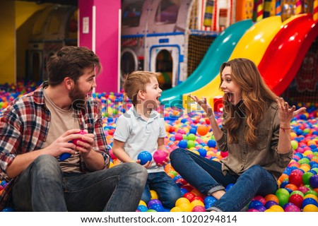 Young happy family with their little son spending time together at the entertainment centre #1020294814