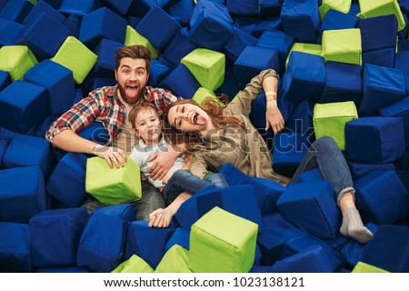 Young happy family with their little son spending time together at the entertainment centre #1023138121
