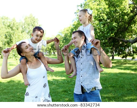 Young happy family with two children in the summer park