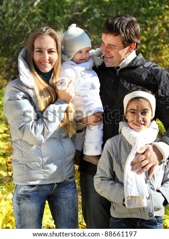 Young happy family with two daughters in autumn forest