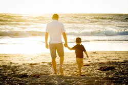 young happy father holding hand of his little son walking on the beach with barefoot in sand in front of sea waves, the kid together with dad looking to the water in Summer sunset coast
