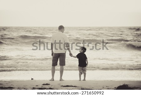 young happy father holding hand of little son walking together on the beach with barefoot in sand in front of sea waves, the kid smiling and having fun  with dad in Summer sunset coast