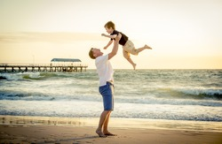 young happy father holding up in his arms little son putting him up at the beach in barefoot standing in front of sea waves wet sand having fun with the kid in Summer sunset coast