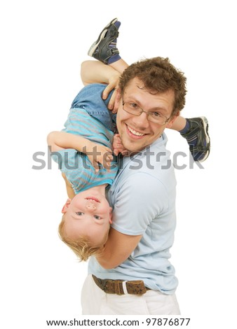 Young happy father in blue t-shirt playing with little smiling son, holds the boy head over heels. Isolated on white.