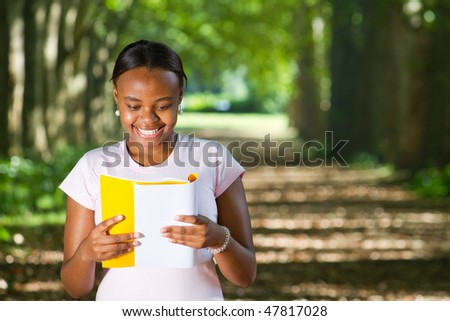 young happy female college student reading book on campus