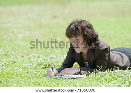 young happy female in blue shirt makes some notes in notepad,