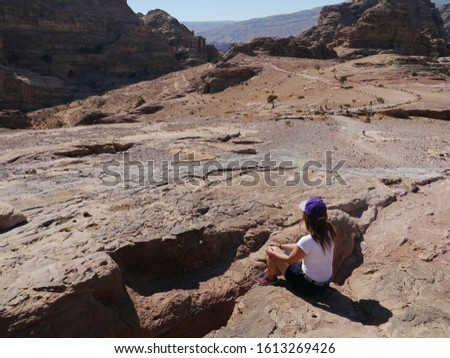 young happy female tourist watching the panoram of famous Al Deir Monastery in the ancient city of Petra. Petra is the main attraction of Jordan. Petra is included in the UNESCO heritage list