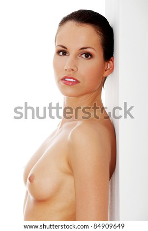 Young, happy, fit, naked woman standing next to white wall