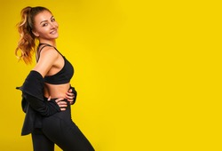 Young happy fitness girl with sporty body posing at studio on a yellow background. Beautiful fit Girl. Fitness smiling model in black sportswear. Weight Loss. Healthy lifestyle. Sporty healthy female.
