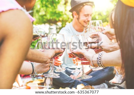 Young happy friends cheering and having fun together in a picnic at backyard - Group of people toasting with red wine - Concept of funny meeting persons - Focus on left hand with glasses