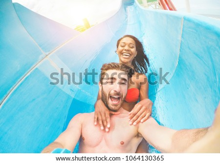 Young happy friends having fun in aqua park pipe  during weekend holidays - Crazy multi race couple taking selfie photo with funny faces - Summer vacation, travel and love concept