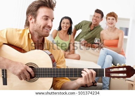 Young happy friends having party, one playing guitar, the others listening.