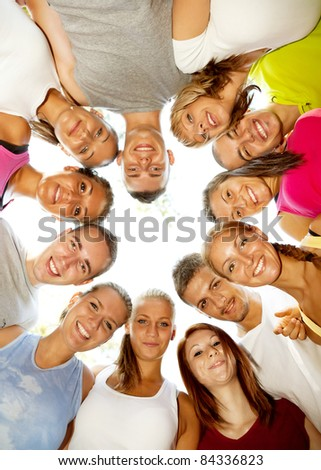 young happy friends with heads together in circle