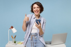 Young happy fun secretary employee business woman in casual shirt work stand at white office desk with pc laptop hold mobile cell phone show thumb up gesture isolated on pastel blue background studio.
